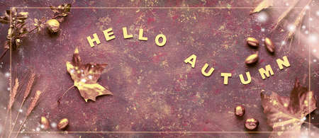 Autumn flat lay with painted golden leaves and text Hello Autumn on dark brown textured bacgkrdound. Panoramic image with frame and light overlays, banner composition.