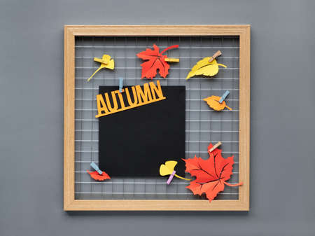 Photo grid board with red and orange paper Autumn leaves and text Autumn on pegs. Paper mockup for your lettering, calligraphy, picture or drawing