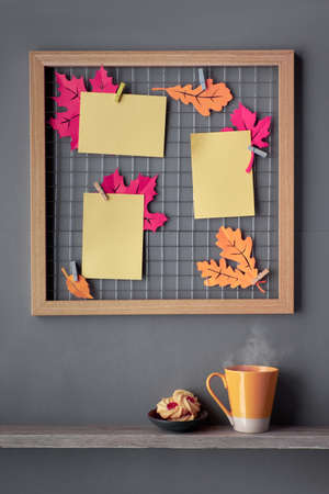 Photo grid board with Autumn paper leaves in fuchsia and orange colors and blank paper cards on pegs. Orange cup and jam cookies on a shelf below the metal grid. Fall-related mockup.