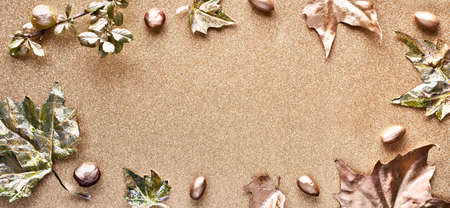 Autumn flat lay with painted golden leaves and copy-space on sparkling golden paper. Top view, panoramic image.
