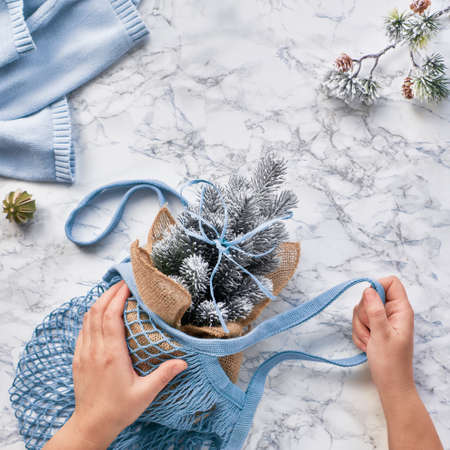 Creative flat lay with artificial plastic Christmas tree in mint blue eco friendly mesh bag. Real or fake Xmas tree dilemma for conscious lifestyle people. Flat lay on marble, square composition
