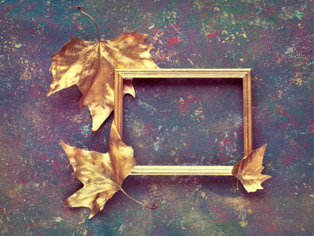 Autumn flat lay with sycamore leaves painted gold around empty golden frame on dark green purple textured background Stok Fotoğraf