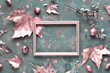 Autumn flat lay with sycamore leaves painted bronze and copy-space in golden frame on dark green textured canvas. Toned image, top view with text space. Stok Fotoğraf