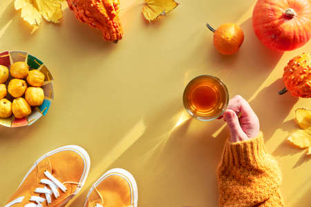 Yellow paper flat lay with copy-space. Female hand with cup of tea, orange pumpkins and paper plate with quince.
