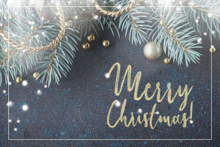 "Christmas tree twigs, trinkets and golden decorations in green and golden colours on dark background, text ""Merry Christmas"""