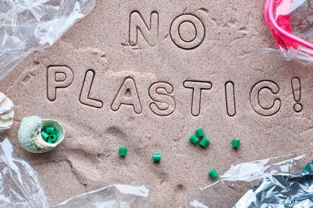 No plastic text on sand framed with various debris. Pollution is harmful to marine lives. Environmental concept. Ban single use plastic campaign.