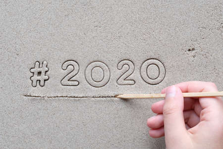 Childs hand drawing hashtag sign and number 2020 on wet sand. Happy New Year 2020!