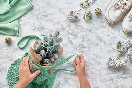 Wintertime, creative flat lay with artificial plastic Christmas tree in eco friendly string or mesh bag. Real or fake Xmas tree dilemma for eco friendly people. Flat lay on light stone background in white and green mint Reklamní fotografie - 130812620