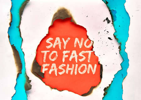 Text Say no to fast fashion in hole burned though white, red and turquoise paper Reklamní fotografie