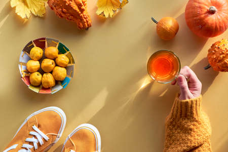 Yellow paper flat lay with everyday objects. Female hand with cup of tea, orange pumpkins, quince and pair of canvas sneakers, top view on yellow paper background. Stock Photo