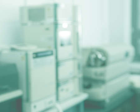 Blurred laboratory interior, scientific background with copy-space. Modern research facility room out of focus. This blurred image toned in tile or light cyan color