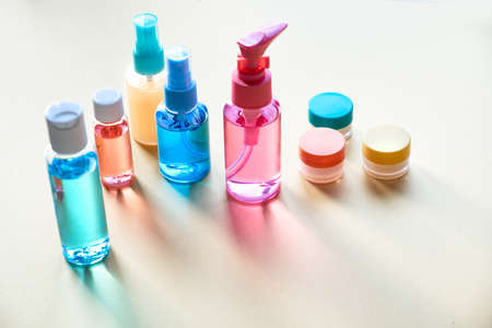 Various toiletries in clear plastic travelling bottles on neutral paper background with long shadows, copy-space Reklamní fotografie