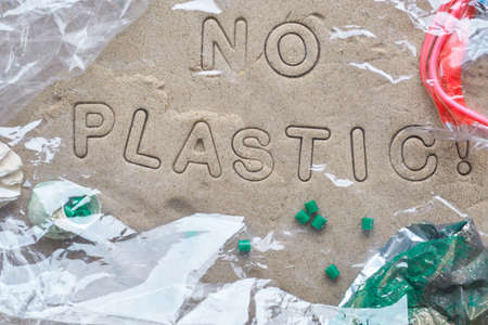 No plastic text on sand framed with various debris and covered with transparent film. Pollution is harmful to marine lives. Environmental concept. Ban single use plastic campaign.
