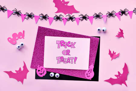 Creative paper craft Halloween flat lay with garland of flags and spiders in magenta and black. Bats, ghosts, chocolate eyes, jack lantern pumpkins, text