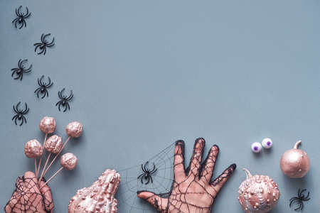 Creative Halloween flat lay on grey paper background with copy-space. Frame made of hands in black mesh gloves imitating spiders with chocolate eyes, holding paint brush, scissors and pumpkins. Banco de Imagens