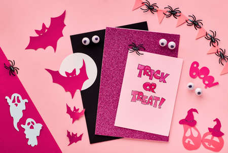 Creative paper craft Halloween flat lay in dark red and black. Top view with bats, ghosts, chocolate eyes, pumpkins, text Trick or treat on cards and paper word Boo.