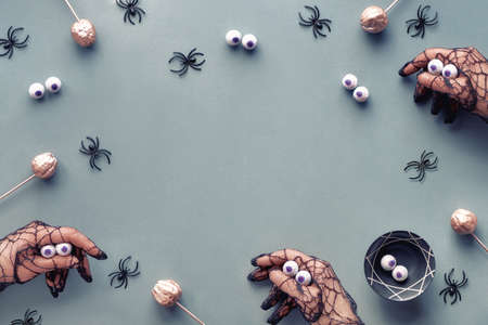 Creative Halloween flat lay in grey, pink and black with decorative pumpkins and spiders. Hands in black mesh gloves imitating monsters, copy-space