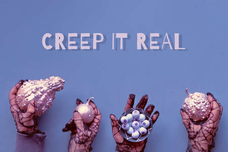 Creative Halloween flat lay in purple and pink. Paper background with text Creep it real.  Hands in black mesh gloves holding decorative pumpkins and chocolate eyes.