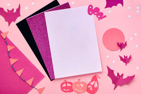 Creative paper craft Halloween flat lay in pink, magenta and black. Top view with cipy-space on stack of cards, bats, chocolate eyes, pumpkins and and word Boo on split paper background.