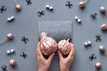 Hands trying to fit two pumpkins on decorative mirror. Creative Halloween flat lay background in grey, pink and black with chocolate eyes and spiders.