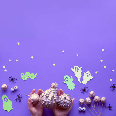 Creative Halloween flat lay on purple paper background with paper ghosts, stars and chocolate eyes. Hands holding gilded pink pumpkins. Square composition with copy-space. Фото со стока