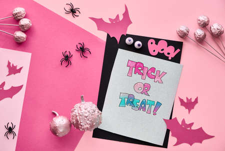 Creative paper craft Halloween flat lay in pink, light purple and black. Top view with stack of cards, bats, chocolate eyes and pink decorative pumpkins. Text Boo and Trick or treat. Фото со стока