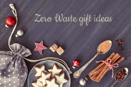 Zero waste gift ideas, text painted on aged grey wooden boards. Top view on Christmas cookies, spices and decorations ready for wrapping in cotton bags with little stars.