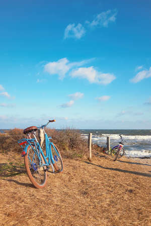 Bikes by the entrance to the beach on island Hiddensee, Baltic sea, Northern Germany. Bright windy day with blue sky and clouds in Autumn or Winter season.