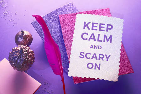 Creative purple and pink Halloween background with levitating pink pin quill, stack of glittering paper and decorative pumpkins painted metallic pink. Copy-space, on the silver paper.