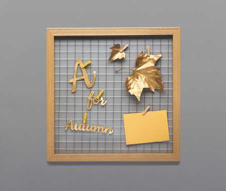"""Fotorasterbrett mit goldenem Herbstlaub, Text """"A für Herbst"""" auf grauer Wand. Platz für Ihr Bild oder Ihre Nachricht auf einer leeren gelben Papierkarte."""