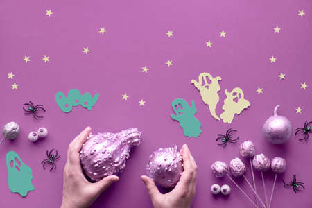 Creative Halloween flat lay on vibrant pink paper background with paper ghosts, stars and chocolate eyes. Hands in black mesh gloves holding pumpkins painted gilded pink.