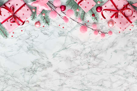 Panoramic Christmas flat lay on white marble with border made from wrapped gift boxes, natural green fir twigs, burgundy and pink trinkets. Copy-space for your text.