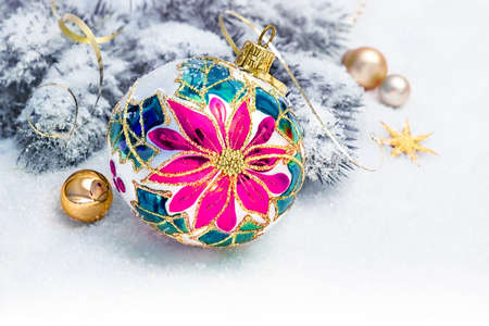 Traditional glass Christmas bauble with pink poinsettia design on decorated branches of Christmas tree on snow with golden trinkets, serpentine and stars.
