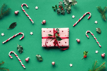 Trendy Christmas flat lay on green paper background with candy canes, fir twigs, wooden stars and trinkets. Gift box wrapped in pink wrapping paper with red ribbon and natural holly twig..