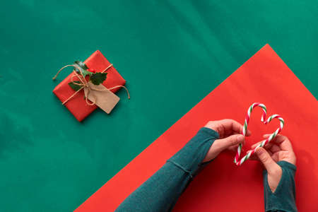 Creative diagonal geometric flat lay on green and red paper with long shadows of leaves. Hands in green t-shirt holding two stripy candy canes in shape of heart. Eco-friendly zero waste Christmas.