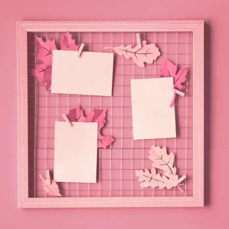 Fotorasterbrett mit Herbstpapierblättern und leeren Papierkarten auf Stiften. Rosa monochromes trendiges Modell für Ihre Bilder oder Beschriftungen, quadratische Komposition.