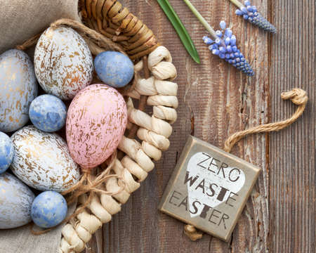 Easter background with eggs, blue hyacinth flowers and wooden heart, top view on rustic wood. Zero waste Easter written on wooden tag with heart. Eco friendly decorations. Stock Photo - 133302483