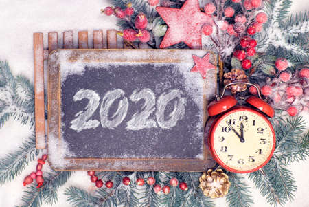New Year flat lay with 2020 on blackboard. Red and green traditional winter decorations, trinkets, star, berries and pine cone on snow. Alarm clock showint five to midnight. Happy New Year!