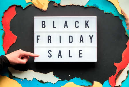 Lightbox text Black Friday Sale in burnt paper hole in white, red, yellow and turquoise paper with burned edges, black paper creative background, hand pointing at the the light box.
