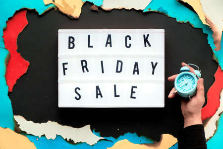 Lightbox text Black Friday Sale in burnt paper hole in white, red, yellow and turquoise paper with burned edges, black paper creative background, hand holding alarm clock.