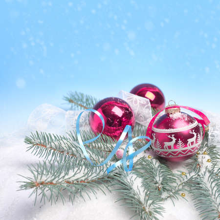 Red and white Christmas bauble and candy canes on abstract winter blue white