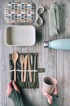 Creative flat lay, zero waste packed lunch with wooden utensils, lunch box, drinking bottle and reusable coffee cup. Sustainable lifestyle top view, flat layout on aged wooden table.