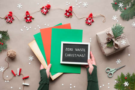 Zero waste Christmas, flat lay, top view on craft paper background with textile doll garland, wrapped gifts, black board with text on stack of colored paper. Eco friendly green Xmas decor.
