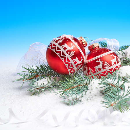 Red and white Christmas bauble and candy canes on abstract winter blue white background with natural fir twigs under snow. Square composition with text space. Merry Xmas and a Happy New Year!