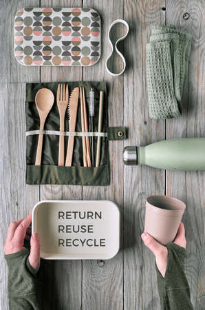 Creative flat lay, zero waste packed lunch concept, reusable wooden cutlery, lunch box, drinking bottle and reusable coffee cup. Sustainable lifestyle top view, flat layout on wooden table, text..