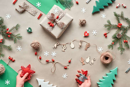 Zero waste Christmas, concept flat layout on rustic wood. Hand crafted gifts, natural Christmas decorations from biodegradable materials, no plastic. Flat lay, top view, hands holding trinkets