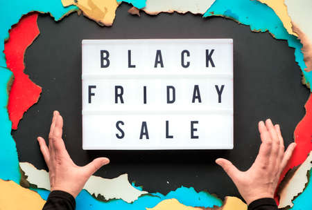 Lightbox text Black Friday Sale in burnt paper hole in white, red, yellow and turquoise paper with burned edges, black paper creative background, hands trying to get the light box.