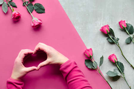 Beautiful trendy geometric flat lay in red and natural colors with pink color roses. Female hands in fluffy pink fleece showing heart shape sign up over. Valentine, mothers day or birthday concept.