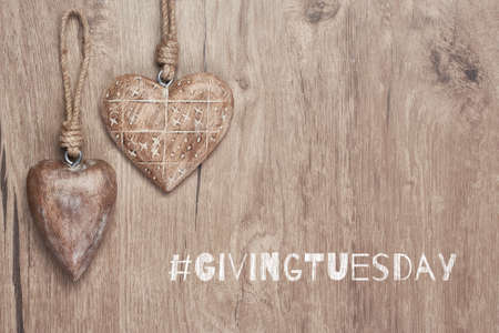 Givingtuesday is a global charity campaign - Black Friday of Charity. Giving Tuesday, global day of charitable giving. Give help, donations and support. Wooden hearts, flat lay on wood with text.