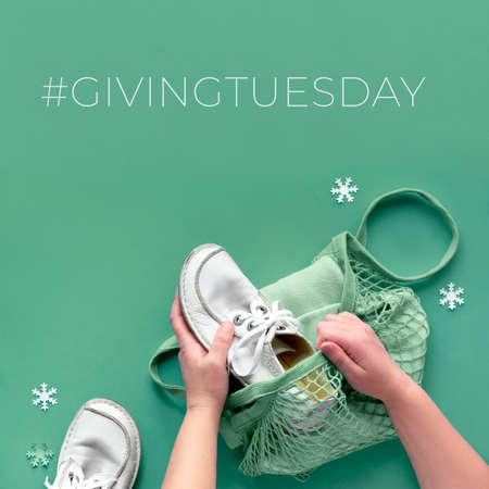 Give goods on Giving Tuesday, participating in donation drive. Collect unwanted goods and pass them on to those in need. Concept flat lay with hands packing shoes and clothes in mesh bag.